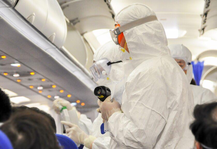 Medycy w kombinezonach ochronnych sprawdzają pasażerów w poszukiwaniu objawów koronawirusa