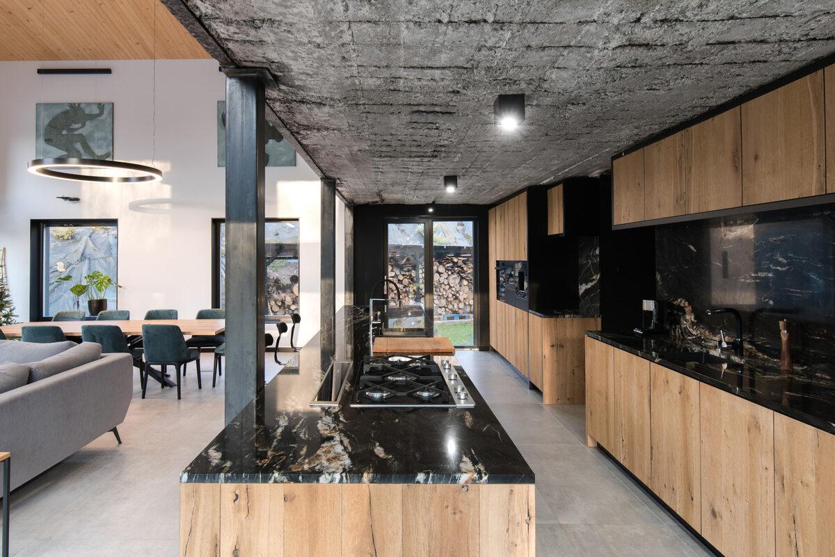 Ślonsko Chałpa Użyte we wnętrzu naturalne i minimalistyczne materiały takie jak gładkie, pięknie usłojone drewno i ciemny polerowany granit świetnie kontrastują, a zarazem uzupełniają się z surowym budulcem czyli nierównymi cegłami czy nieobrobionym betonem z widocznymi śladami po cięciu.